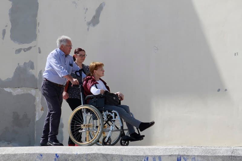 father and daughter traveling with mother in wheelchair